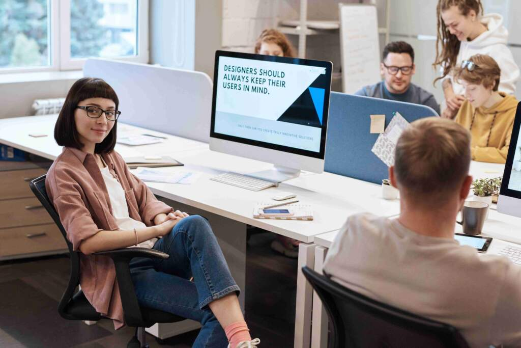 Designers should always keep their users in mind | Group of people working around long desk with computers and notebooks | Affordable graphic design services
