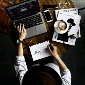 Person working at desk with computer, notebook, and cup of coffee | Affordable graphic designers